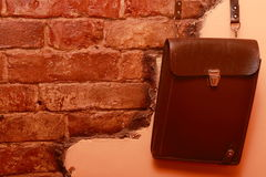 Leather bag on brick wall. Brown leather bag hanging on brick wall background Stock Images
