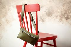 Leather bag on chair. Against light background Royalty Free Stock Images