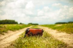 Leather bag on country road Royalty Free Stock Image