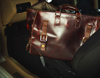 Leather bag and a luxury car Stock Photos