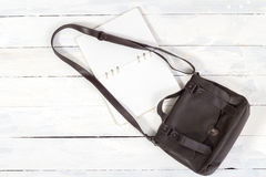 Leather bag with notebook. On white wooden background Stock Photo
