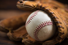 Leather baseball glove and ball on a wooden bench. Brown leather baseball glove on a wooden bench Stock Image