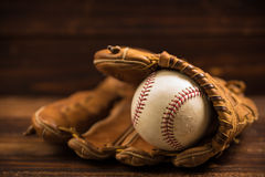 Leather baseball glove and ball on a wooden bench Stock Images