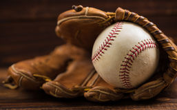 Leather baseball glove and ball on a wooden bench. Brown leather baseball glove on a wooden bench Stock Photo