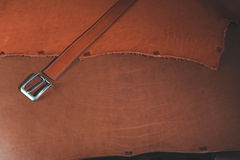 Leather belt with buckle over leather background. Stock Image