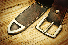 Leather belt with a buckle. On a wooden board. Toned Stock Photos