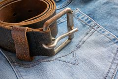 Leather belt with metal buckle on blue jeans royalty free stock photography
