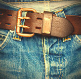 Leather belt on old jeans. Clasped leather belt on old blue jeans, instagram image style Royalty Free Stock Photography