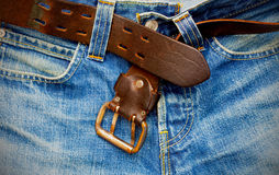 Leather belt on old jeans. Unfastened leather belt on old blue jeans Royalty Free Stock Photos