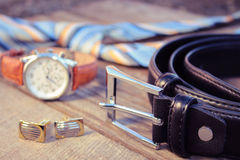 Leather belt, tie, cufflinks and watches on the old wood background. Toned image stock image
