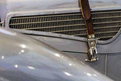Leather belt on vintage oldtimer gray car on radiator grill stock image