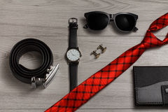 Leather belt, watch, sunglasses, red silk tie, cufflinks, notebo Stock Photos
