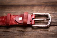 Girdle of red leather. Fashionable leather belt on a wooden tabl royalty free stock image