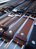 Leather belts. A closeup of leather belts in various shades of black and brown, laid out on a table stock image