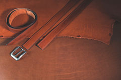 Leather belts with buckle over leather background. Royalty Free Stock Images