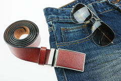 Leather belts, jeans, sunglasses on white background Stock Photos