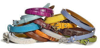 Leather belts. New multi-colored leather fashion belts are on the table isolated on white background Stock Image