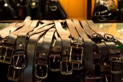 Leather belts in rows stock photos