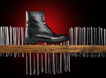 Leather black boot on black background with red backlight. The boot stands on the wooden board and pushes the nails. conceptual and creative shoe picture. Man Royalty Free Stock Photos