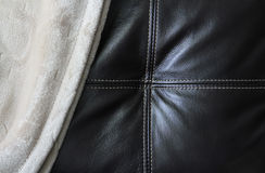 Leather & Blanket. Close up of a polyester blanket over a leather sofa Royalty Free Stock Images