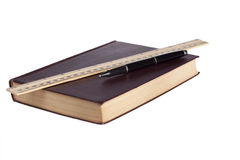 Leather book with black pen and wooden ruler. On white background Stock Photography