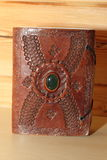 Leather book in oriental style. Brown leather book with a green stone in oriental style Stock Photo