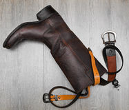 Leather boots and belts. In wooden background Royalty Free Stock Photography
