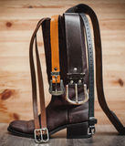 Leather boots and belts. In wooden background Stock Photos