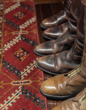 Leather Boots and Carpet. Worn Leather Boots with Patterned Carpet Royalty Free Stock Photo