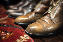 Leather Boots and Carpet. Worn Leather Boots with Patterned Carpet royalty free stock image