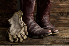 Leather boots and gloves. A concept image of worn cowboy boots and gloves royalty free stock image