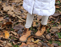 Leather boots of a little girl on the dry leaves Royalty Free Stock Photo
