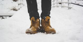 Leather boots in the snow Royalty Free Stock Photo