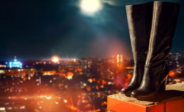 Leather boots standing on roof overlooking city at night Stock Photos