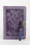 Leather bound purple journal and pen Royalty Free Stock Image