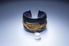 Leather bracelet with gold chain with pearl element Stock Photo