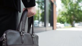 Leather briefcase in the hand of a walking person