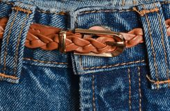 Leather brown braided belt tucked into jeans close-up.  stock images