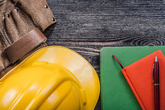 Leather building belt note-books pen hard hat on wooden board co Royalty Free Stock Image