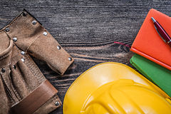 Leather building belt note-books pen yellow hard hat on wooden b Stock Photo
