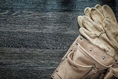 Leather building belt pair of protective gloves on black board Stock Image