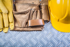 Leather building belt protective gloves hard hat on grooved meta Royalty Free Stock Photography