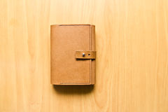 Leather case notebook. On wood background royalty free stock photography