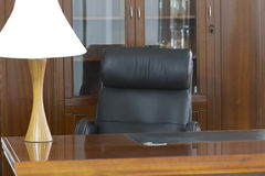 Leather chair behind a desk. Black leather chair behind a desk Stock Photo