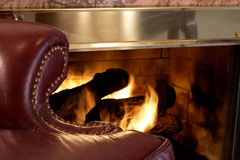 Leather chair by the fire Stock Images