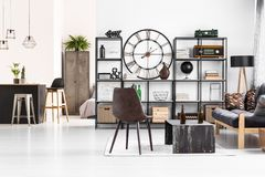 Leather chair in manly flat. Leather chair standing next to an industrial table with beer bottles on it in manly flat interior with open living room Stock Photo