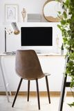 Leather chair standing by wooden desk with mockup monitor, metal lamp and decor in real photo of home office corner in white room. Interior stock photos