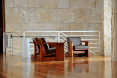 Leather chairs and marble wall. Leather chairs on wood floors in a marble walled building Stock Photos