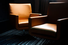 Leather chairs. Two orange business style leather chairs aranged close together in darkness and lit from above Stock Photo