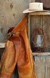 Leather chaps, cowboy hats, lantern on shelf Royalty Free Stock Image